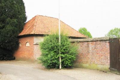 Koetshuis met muur van voormalige turfopslag bij kerk in Lattrop